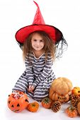Little girl Witch in hat with pumpkins and candy isolated on white