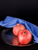 Juicy ripe pomegranates on wooden table, on dark background
