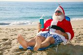 Santa Claus relaxing in his lounge chair on a tropical sandy beach - Christmas concept  Santa Claus loves to vacation when not having to work on Christmas Eve delivering gifts to good boys and girls.