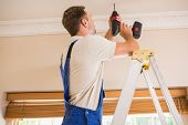 Handyman using a cordless drill to the ceiling in a new house