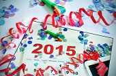 foto of confetti  - a tablet with a picture of a 2015 calendar on an office desk full of confetti - JPG