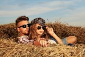 stock photo of haystack  - Romantic young couple in casual clothes sitting together in haystack - JPG