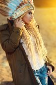 Portrait of a beautiful girl in style of the American Indians on a sunset. Western style. Jeans fashion.