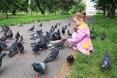 Little girl feeding pigeons.