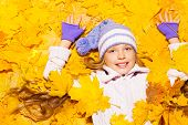 Little girl lay in autumn maple leaves