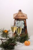 New Year's still-life with a small lamp, sparkling, a fur-tree branch and tangerines