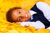 Little African boy lays on autumn yellow leaves