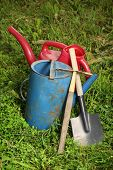 Old Watering Cans And Shovel On Grass