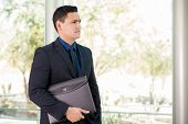 pic of laws-of-attraction  - Handsome young lawyer carrying documents in a portfolio and looking towards copy space - JPG