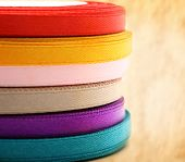 Reels Of Ribbon On Stained Paper Background