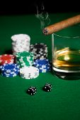 gambling, fortune and entertainment concept - close up of casino chips, whisky glass, dice and smoking cigar on green table surface