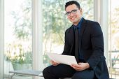 picture of laws-of-attraction  - Attractive young businessman wearing glasses and reviewing some documents at work - JPG