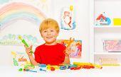 Cute preschool blond boy with toy work tools