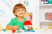 Smart little boy build toy plastic blocks house