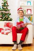 Young teen boy with many presents on the sofa