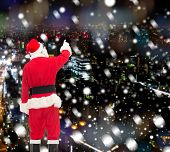 christmas, holidays and people concept - man in costume of santa claus pointing finger from back over snowy night city background