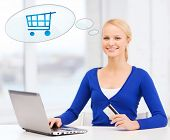 online shopping, people and technology concept - smiling young woman with laptop computer, credit card and text bubble with trolley