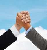 business, people and competition concept - close up of two people hands armwrestling over blue sky and white cloud background