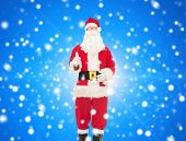 christmas, holidays, gesture and people concept- man in costume of santa claus showing thumbs up over blue snowy background