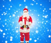 christmas, holidays and people concept - man in costume of santa claus with gift box over blue snowy background