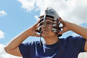 Man In Blue Shirt Wears Medieval Helmet With Leather Straps On Sunny Day