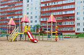 Colorful Playground In Sand Next To High-rise Residential Building