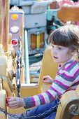Beautiful Little Girl Rides On Carousel Pirate Ship In Summer Park