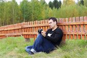 Man With Camera Sits On Grass Near Orange Wooden Fence At Autumn Day