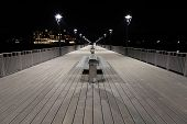 Night View Of A  Boardwalk, Bench And Lamp Posts.