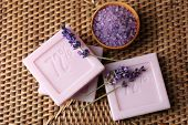 Bars of natural soap with fresh lavender on wicker mat background