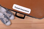 Travel suitcase with inscription travel insurance on wooden background