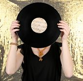 Young woman holding retro record in front of face, on shiny background