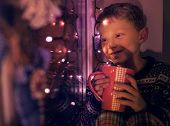Little Boy With Big Cup Of Hot Drink Looks On The Window With Christmass Lights