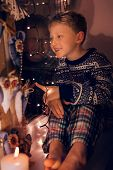 Smiling Little Boy On The Window In Christmas Time