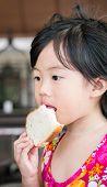 Cute Little Girl Eating Bread