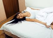 pretty indian brunette in bed smiling, white sheets