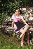 Girl in dirndl sunning himself on a bench
