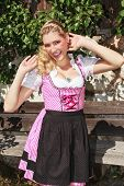 Flirty blond bavarian girl in dirndl