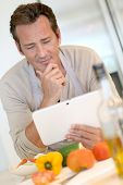 Handsome man in kitchen looking at digital tablet for recipe