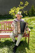 foto of accordion  - Old man enjoying playing accordion in his garden on sunny day - JPG
