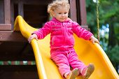 Curly Blonde Girl Sliding At Playground