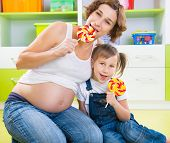 Pregnant Mothe Rand Daughter With Lollipops
