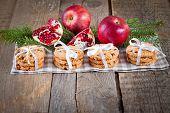 Pomegranate fruit, cookies and apples on wooden background