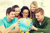 education, travel and geography concept - five smiling student looking at earth globe at school