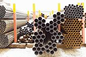 Piles Of Different Pipes In Outdoor Warehouse