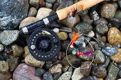 Fly Fishing Pole And Reel With Flies On Wet Stones