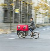 Young Mother Transports Her Child In A Bicycle Buggy In Berlin