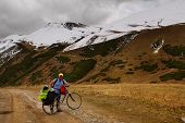 Cyclist On The Background Of Snow Mountains