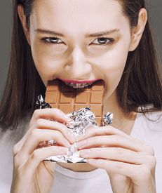 picture of bulimic  - cute young female with chocolate close up eating - JPG