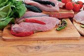 stock photo of kale  - fresh raw turkey meat steak fillet with vegetables kale tomatoes lettuce red hot chili pepper and dark olives on cutting board over wooden table - JPG
